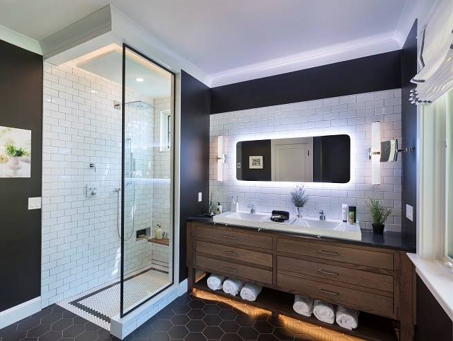This bathroom has a walk-in shower and a wooden vanity with two sinks and an illuminated mirror.