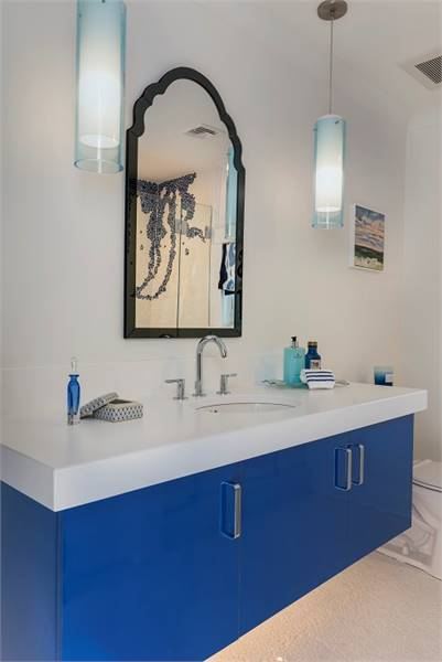 Another bathroom with a blue vanity topped with an arched mirror and cylindrical pendants.