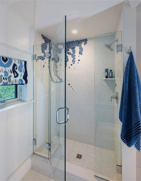 The walk-in shower has white walls, chrome fixtures, a floating shelf, and a glass hinged door.