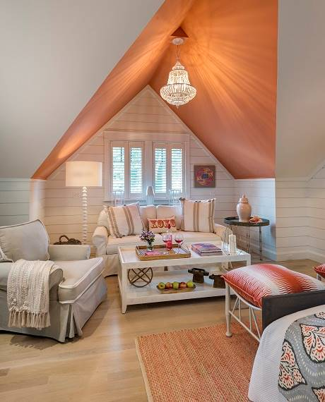 The orange vaulted ceiling adds a pop of color to the guest room.