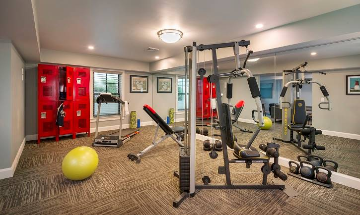 A fully-equipped gym with red lockers, carpet flooring, and gray walls.
