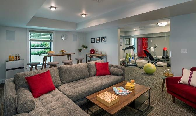 The recreation room opens to the home gym. It has a dining area and comfy seats.