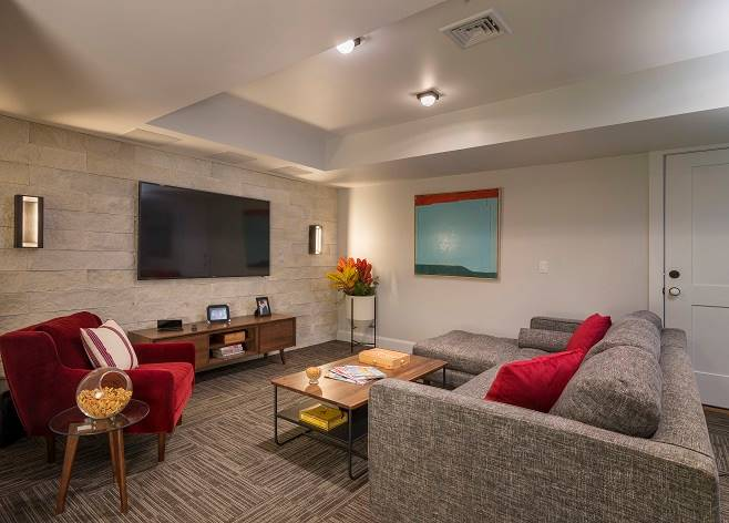 The opposite view reveals the flatscreen TV mounted against the brick accent wall.