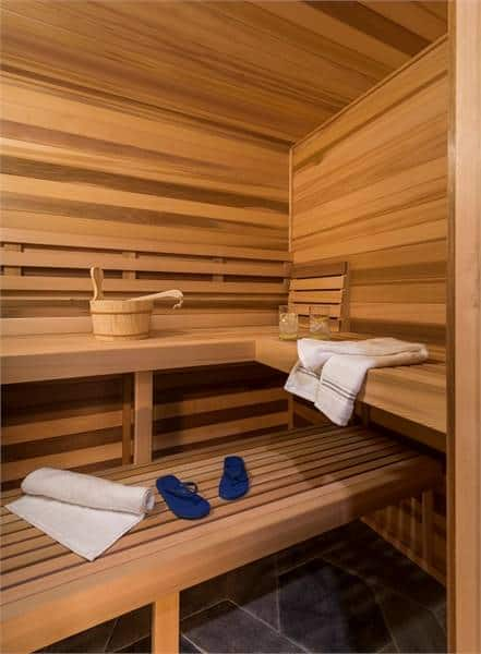 Sauna room with wood plank seat and built-in shelves.