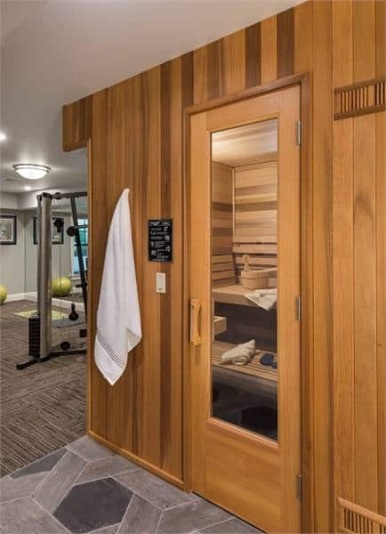 The sauna room with a glazed door sits next to the home gym.