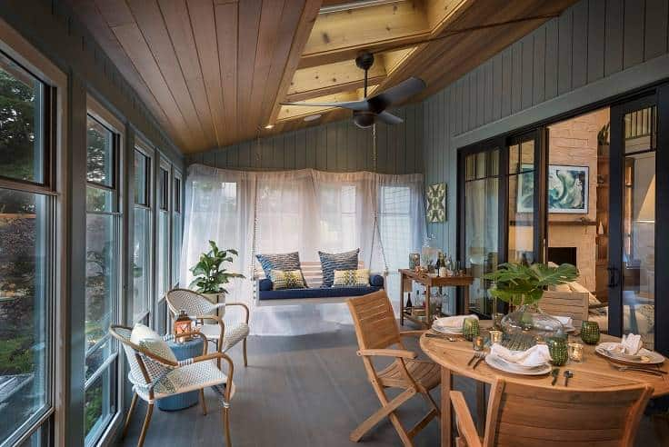 The sunroom is filled with a round dining set, round back chairs, a hanging bench, and skylights.