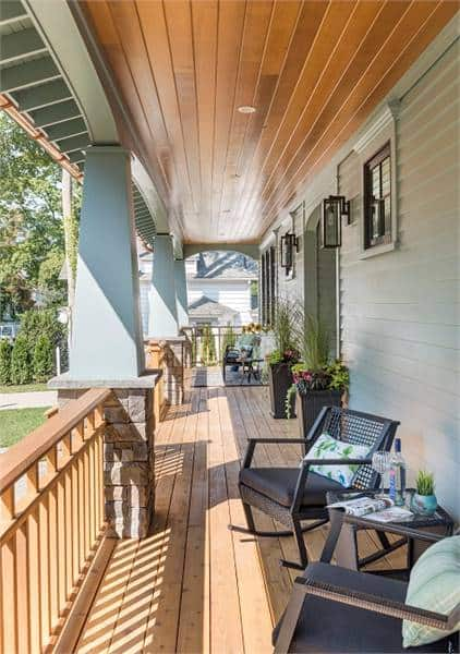 Covered porch with dark wood rocking chairs over wide plank flooring.