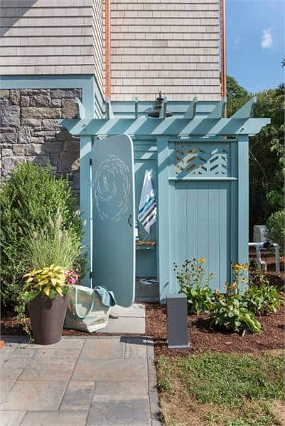 An outdoor shower with blue wooden walls and door attached to the garage.