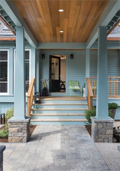 Back porch with a blue stoop placed behind the tapered columns.