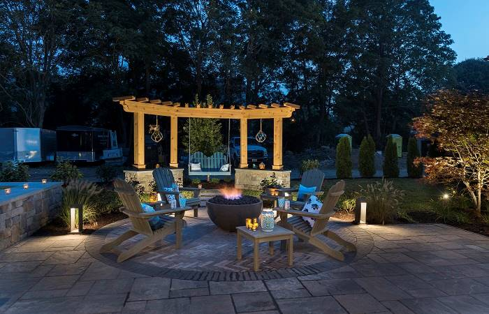 Night view of the open patio showing the warm glow from the outdoor lamps and concrete fire bowl.