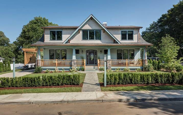 Front exterior view showing the rustic siding and a wide covered porch framed with tapered columns and wooden railings.