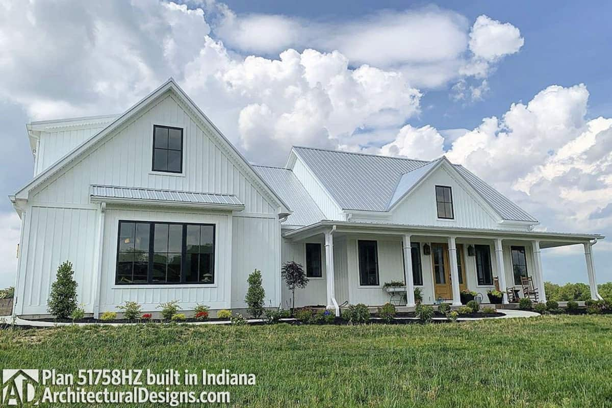 Home facade with a combination of horizontal and vertical siding and a covered porch framed with white pillars.