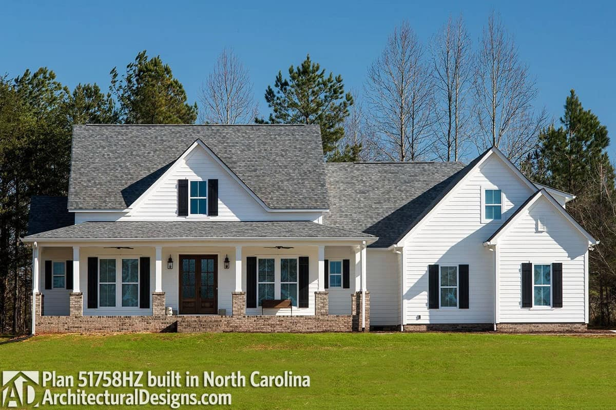 This home showcases white siding, brick accents, and multiple gables.