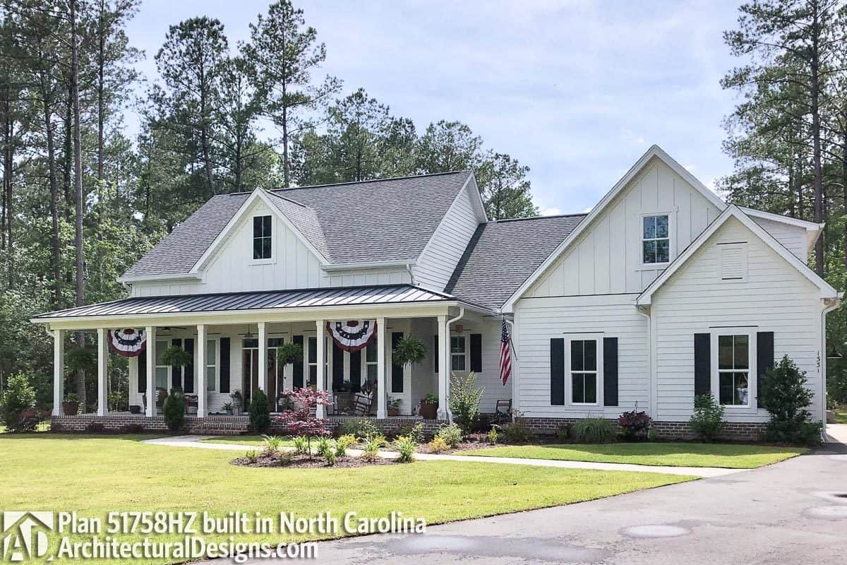 Decorative flags, white pillars, and black shutters adorn the home's facade.