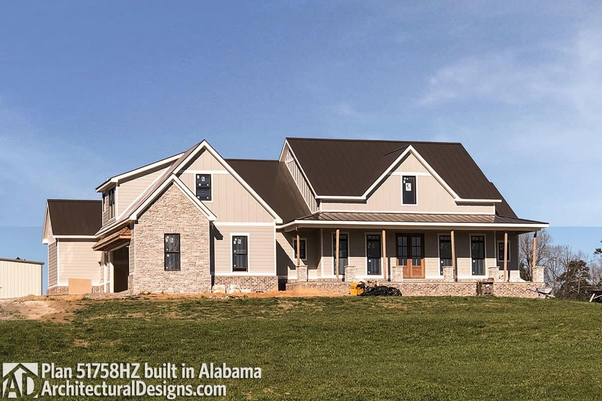 This home showcases a mixture of stone and taupe siding along with a raised porch bordered by wooden columns.