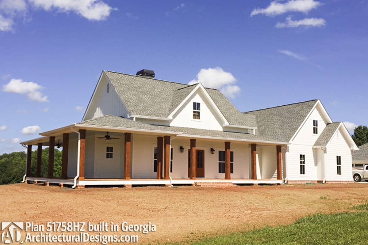 Angled side view of the house showing the multiple gables and wrap-around porch lined with rustic pillars.