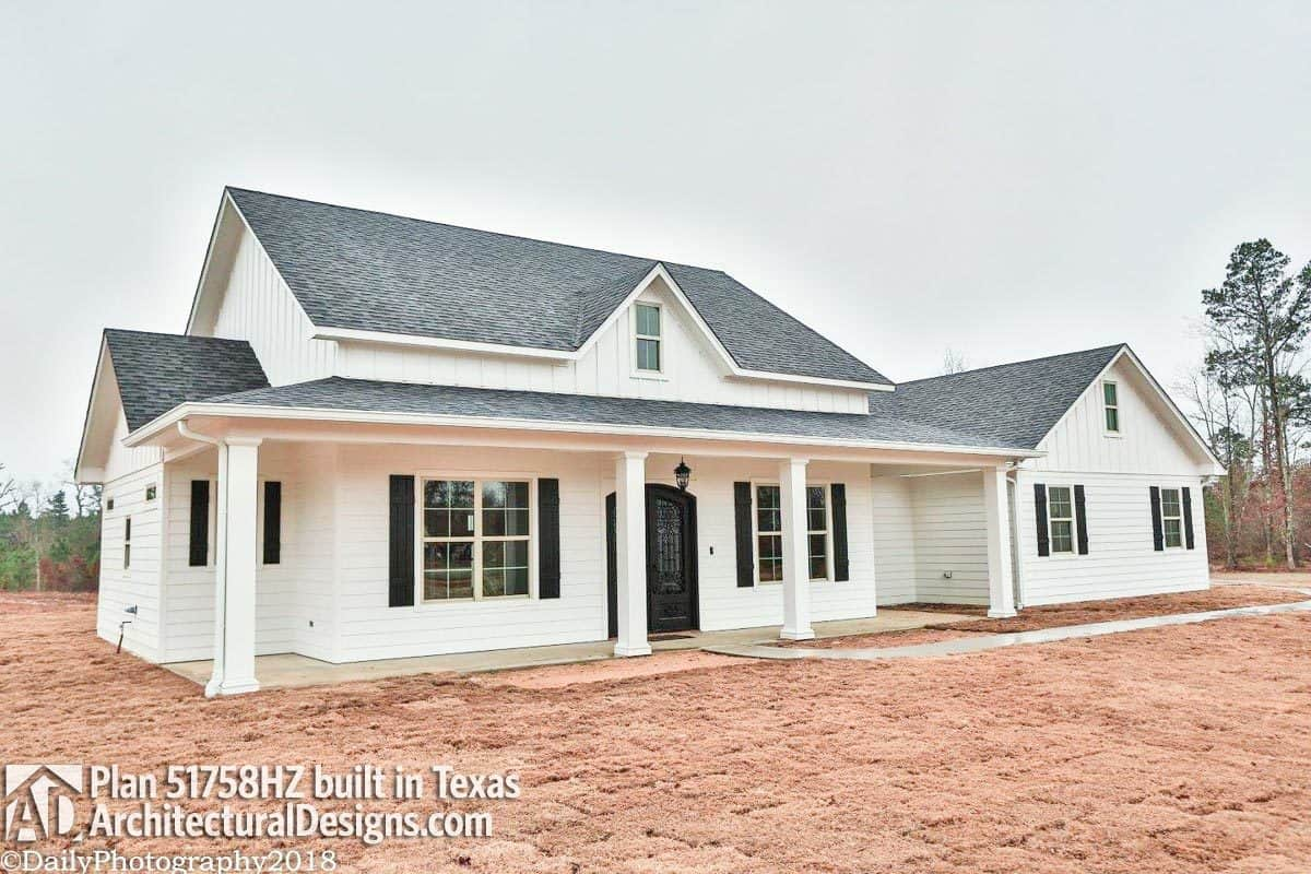 This home has vertical and horizontal siding, tiled roofs, barn shutters, and a wide covered porch.