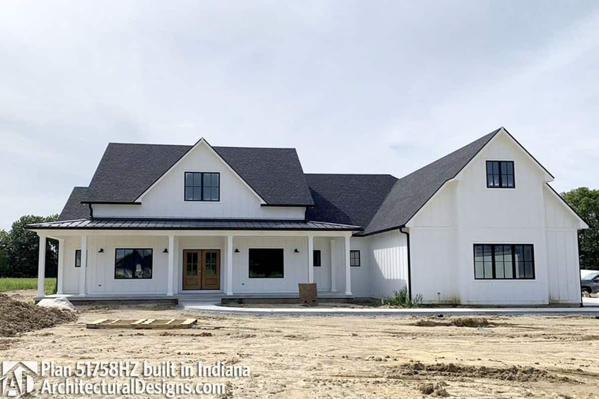 Board and batten siding, black aluminum framed windows, and a french entry door creates a character to the home.