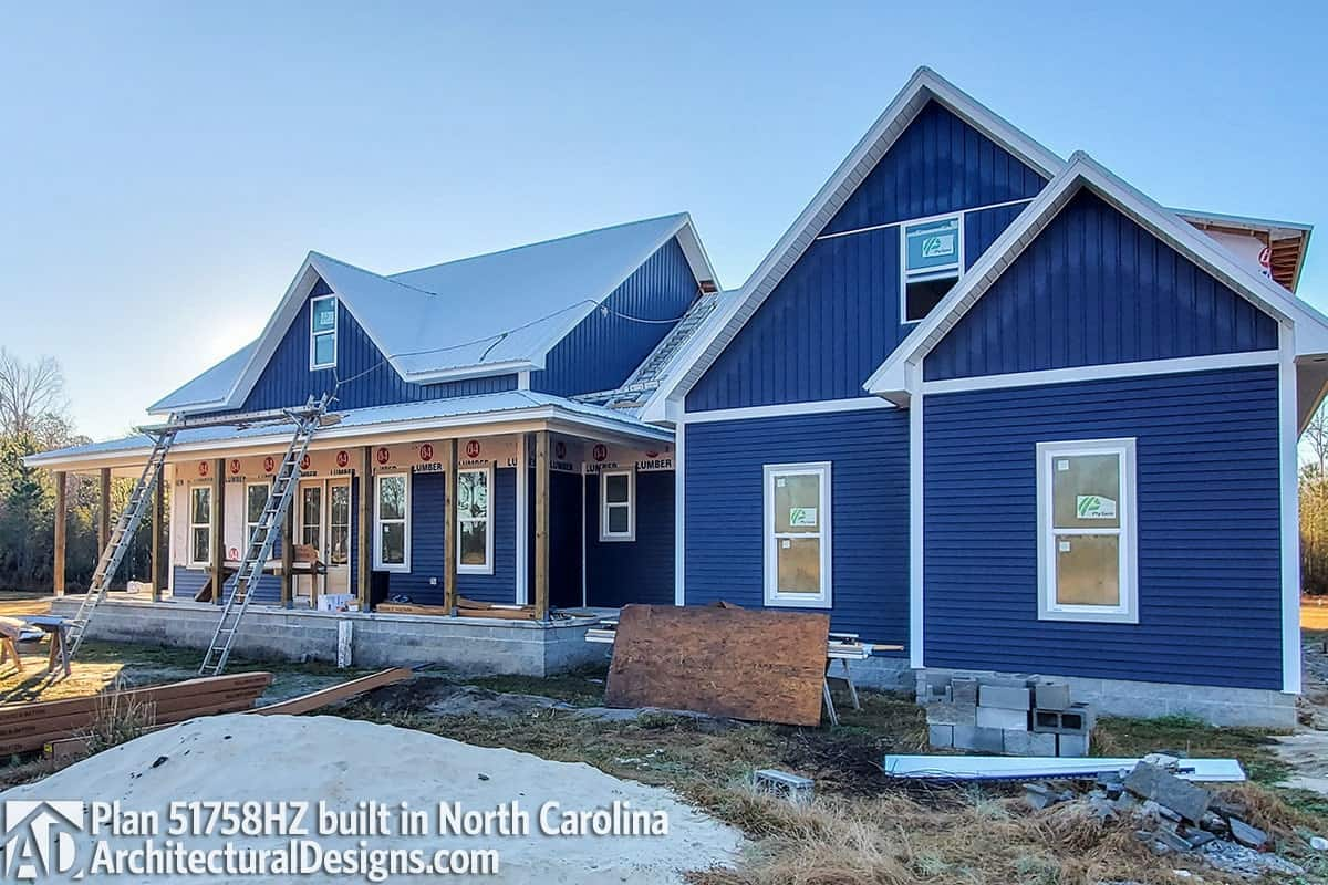 This home has a nice blue siding, white-framed windows, and rustic pillars encasing the covered porch.