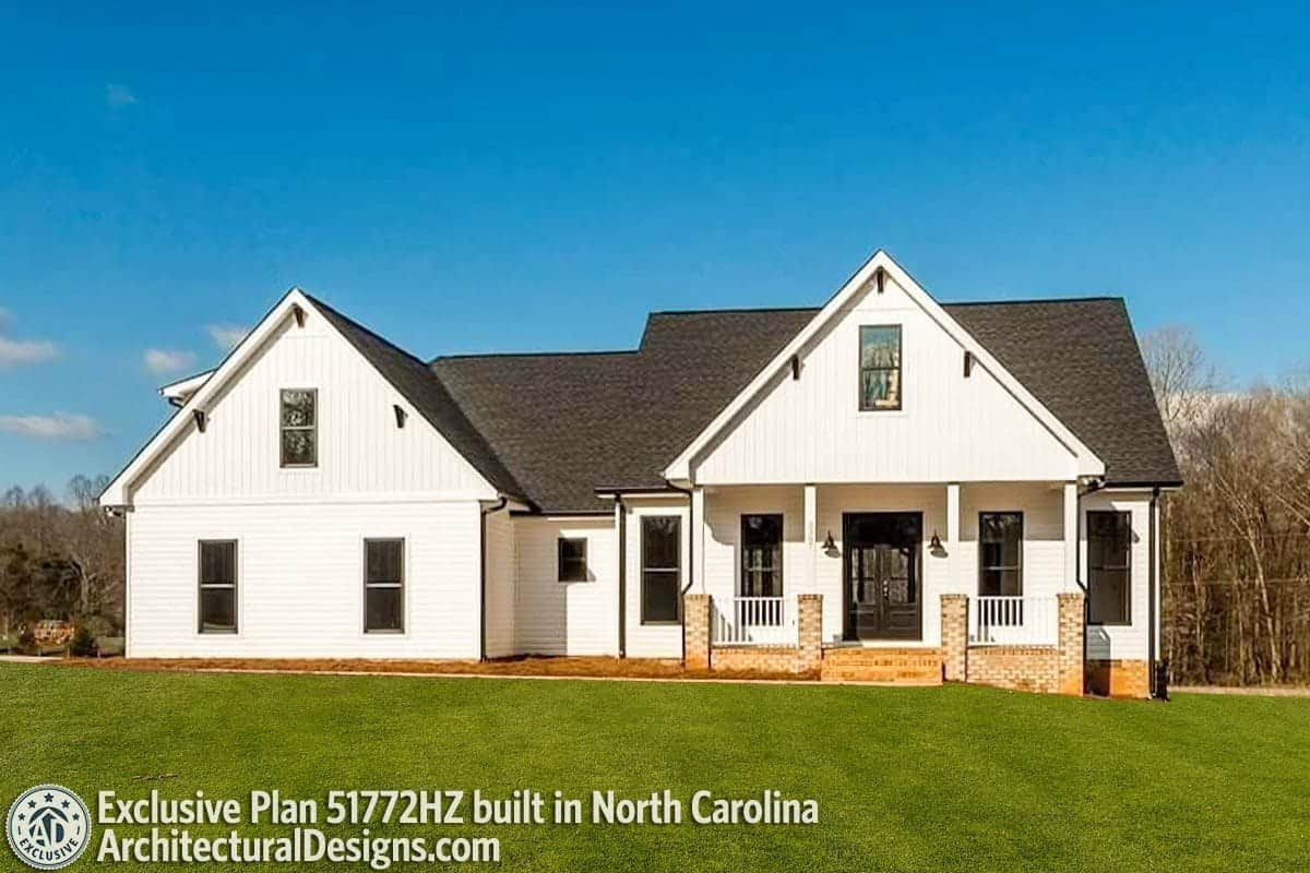 Alternate exterior with white siding, brick bases, and a raised porch bordered by tapered columns and white railings.