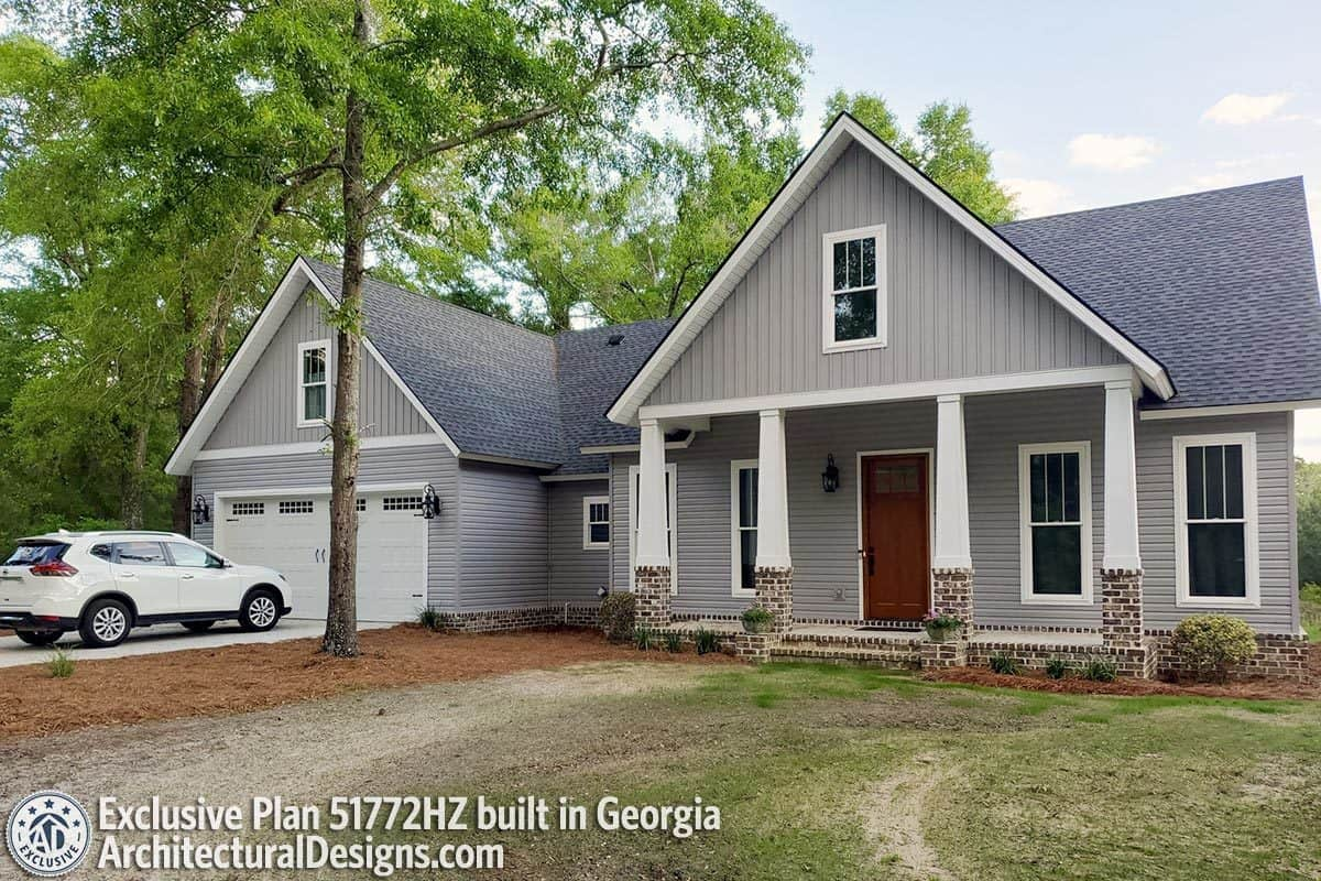 This home has gray siding, gable rooflines, tapered columns, and a front-entry garage.