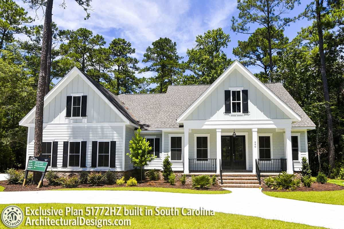 Wrought iron railings, decorative columns, and barn shutters adorn the home's white facade.