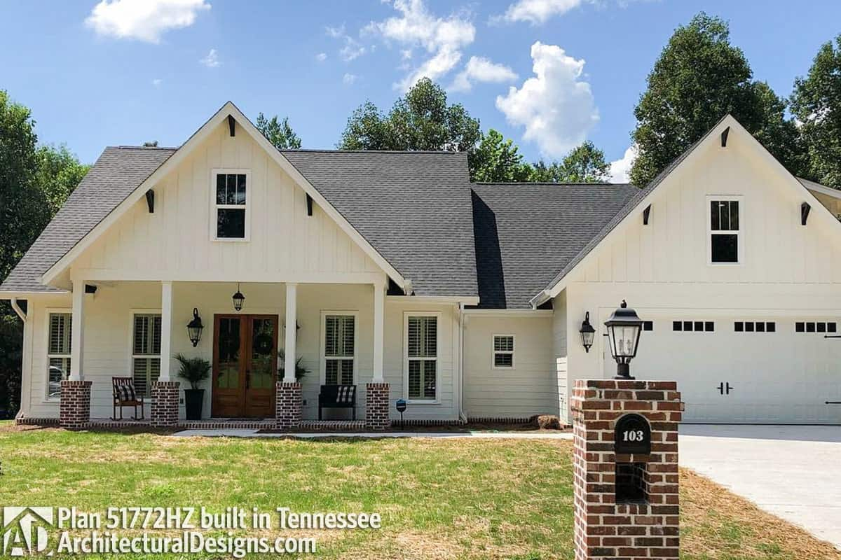 This home features a pristine white siding contrasted by brick columns and a wooden french front door.