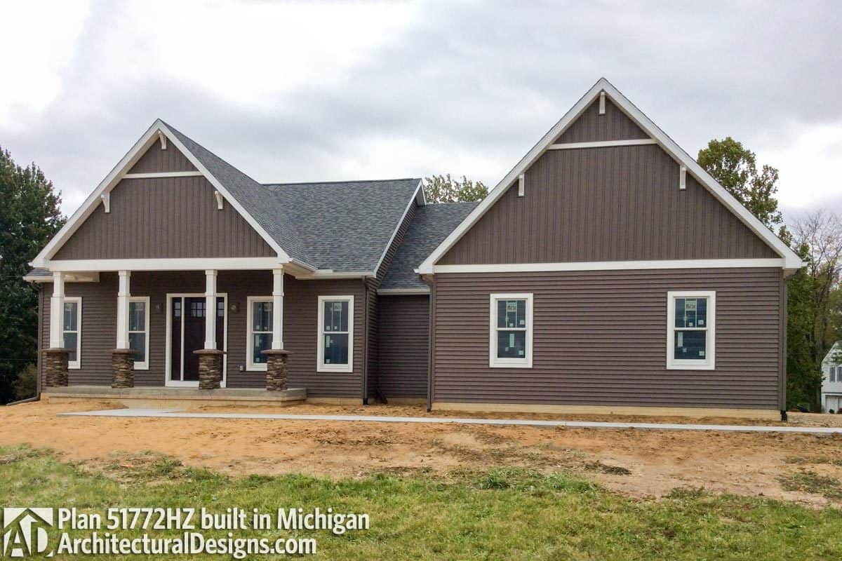 This home has tapered columns, brown siding, and gable roofs graced with white brackets.