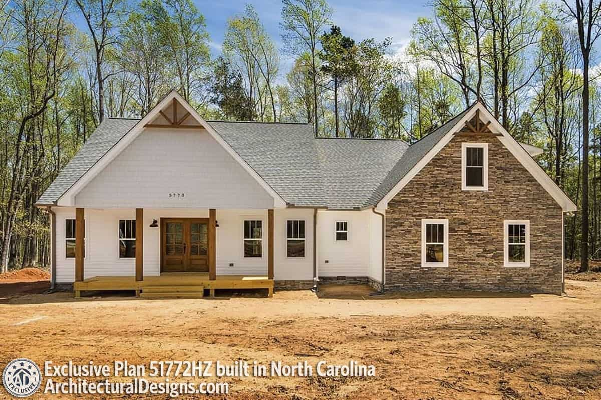 Alternate exterior with stone and white siding, wooden trims, and a raised front porch framed with rustic columns.