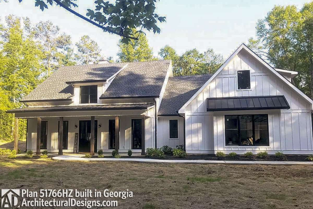 This home has a vertical lap siding, metal awnings, and dark wood pillars framing the front porch.