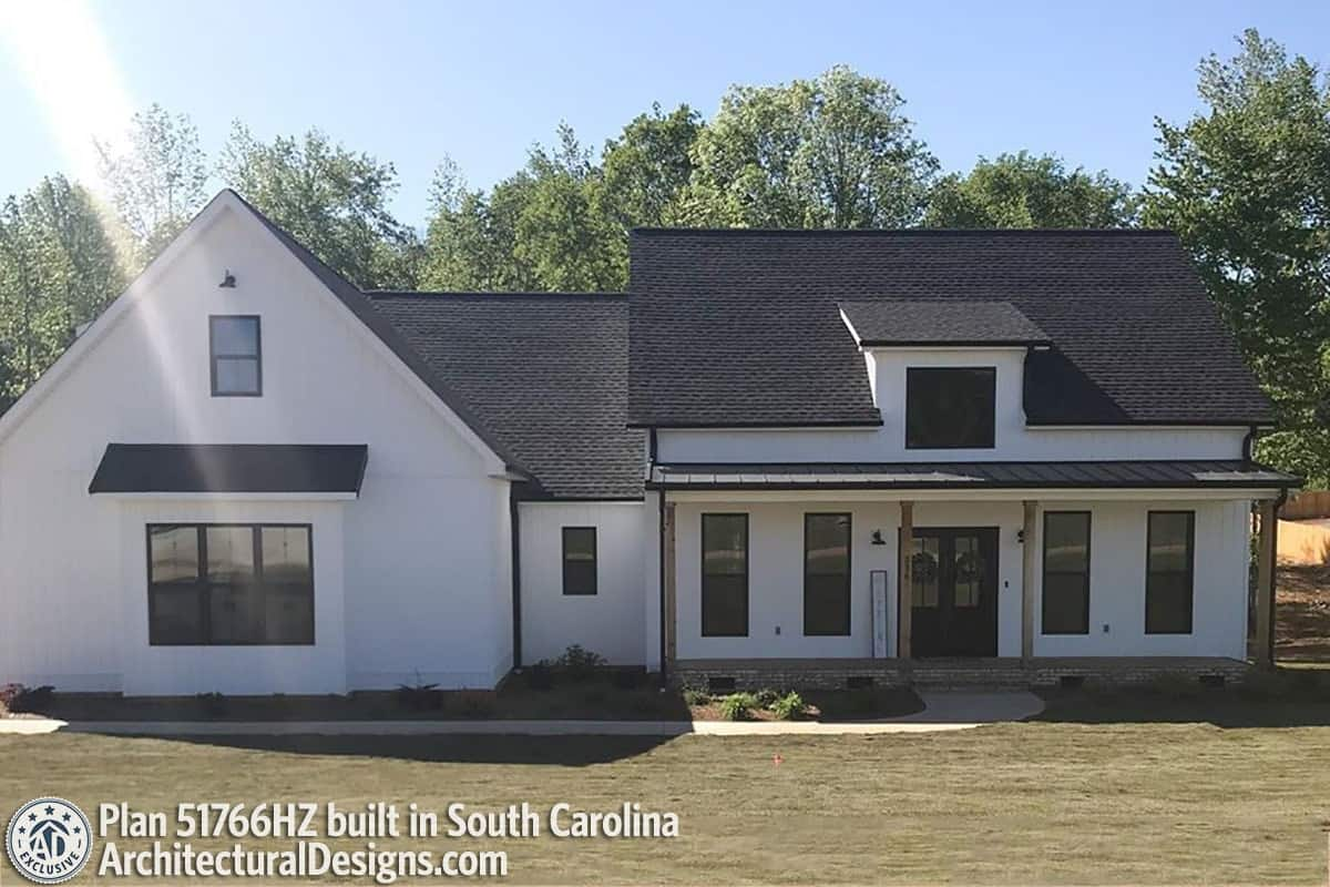 This home showcases a white board and batten siding, tinted glass windows, and a wide porch topped with a shed dormer.