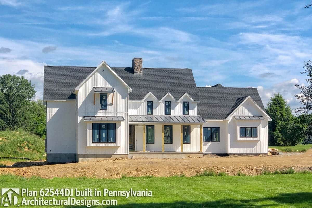 This home has gable rooflines, a stone chimney, and slim wooden pillars framing the front porch.