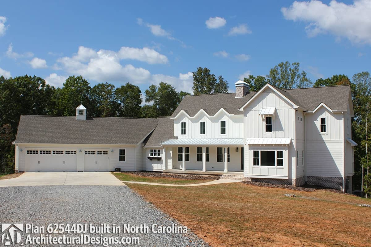 This home has a white board and batten siding, a raised covered porch, and an angled garage topped with a ridge turret.
