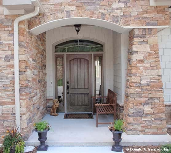 Home entry with a wooden bench and a rustic front door surrounded by glass panels and an arched transom.
