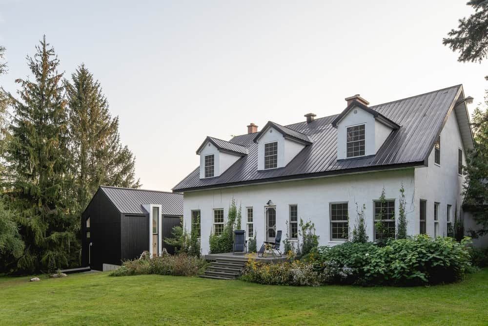 This is a look at the front of the house with a traditional style that contrasts the dark and minimalist extension structure on the side.