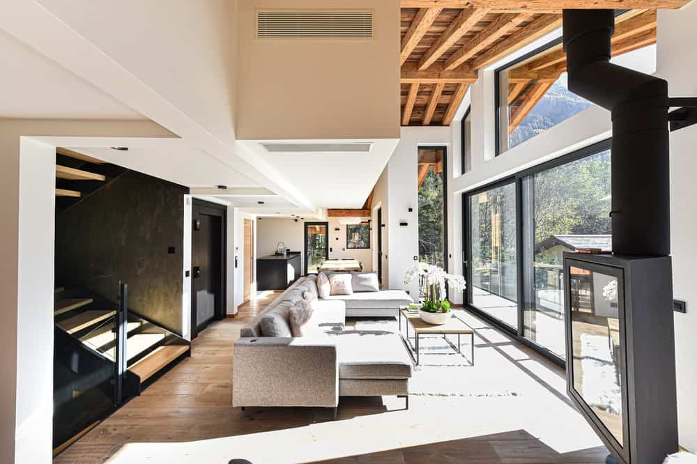 This is a look at the interior of the living room with a large sectional gray sofa paired with a coffee table bathed in natural lighting.