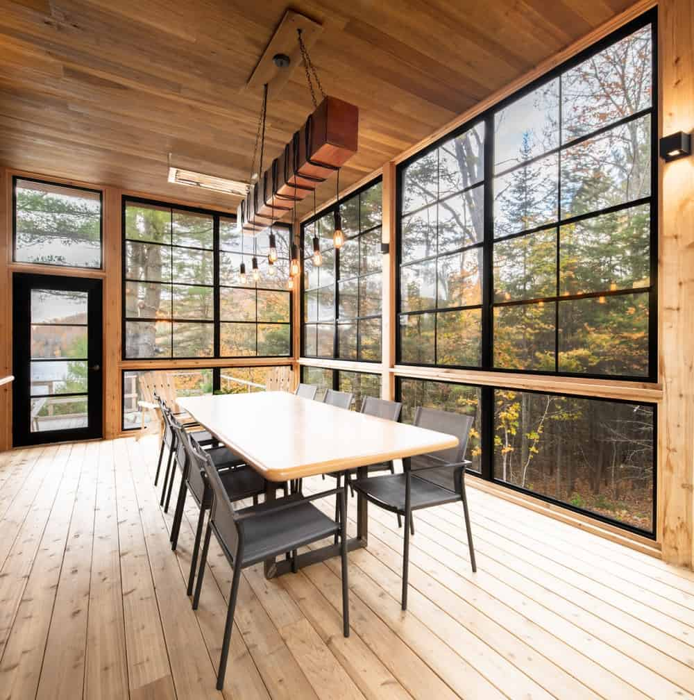 This is the large dining room with a large rectangular dining table surrounded by large glass walls and topped with a row of modern lighting hanging from a wooden shiplap ceiling.