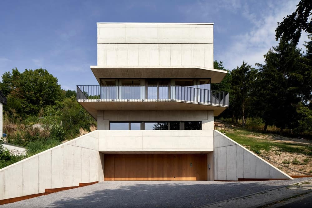 This is a front view of the house that has white exterior walls, wide glass walls and a wrap-around balcony with wrought iron railings.