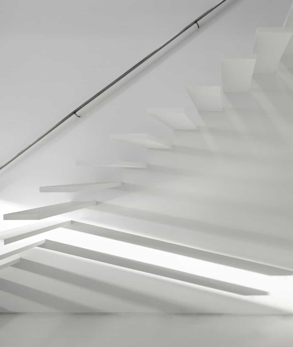 This is a closer look at the modern white staircase that has white steps blending with the white wall.