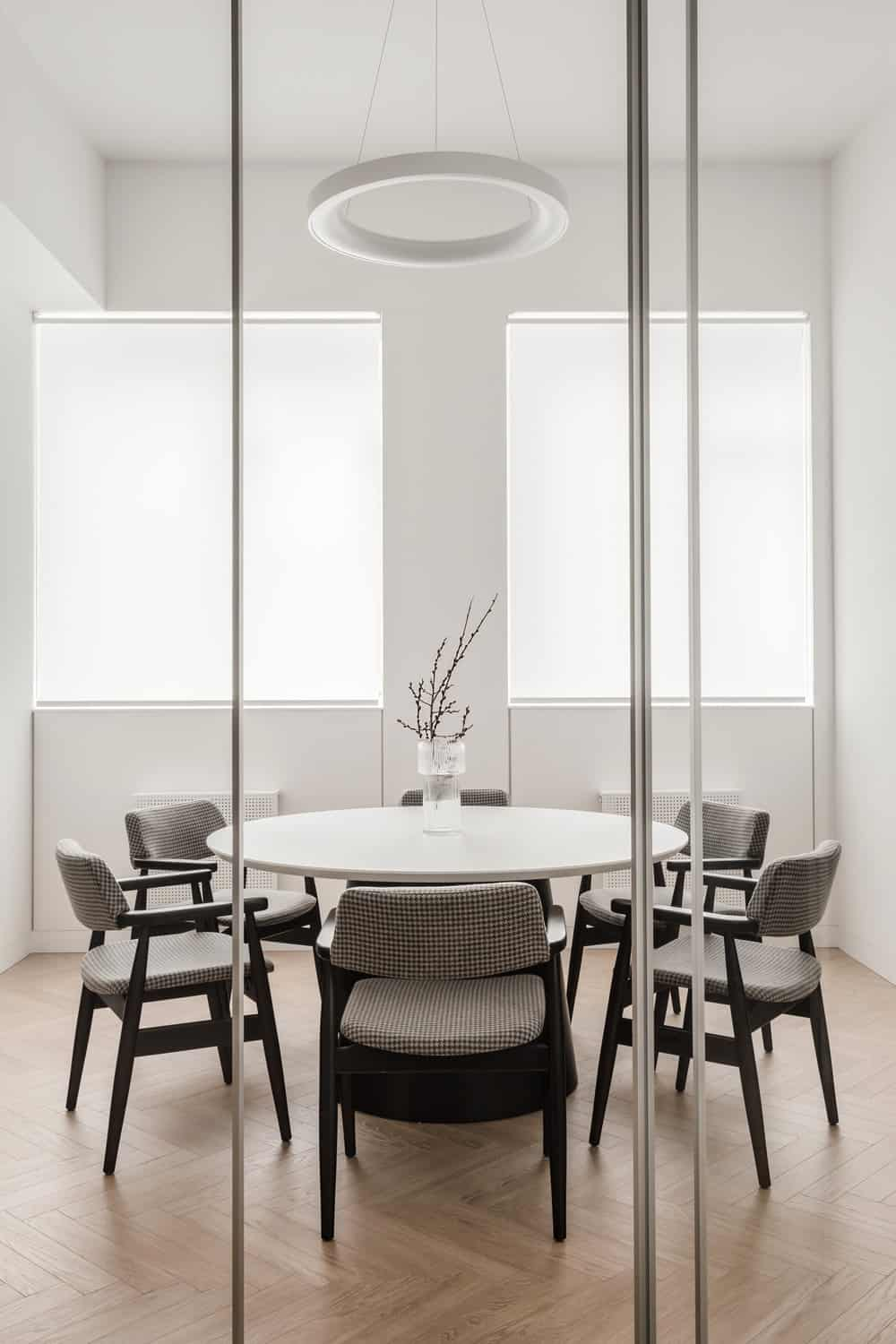 The conference room has a large round table with a lighting hanging from the ceiling.
