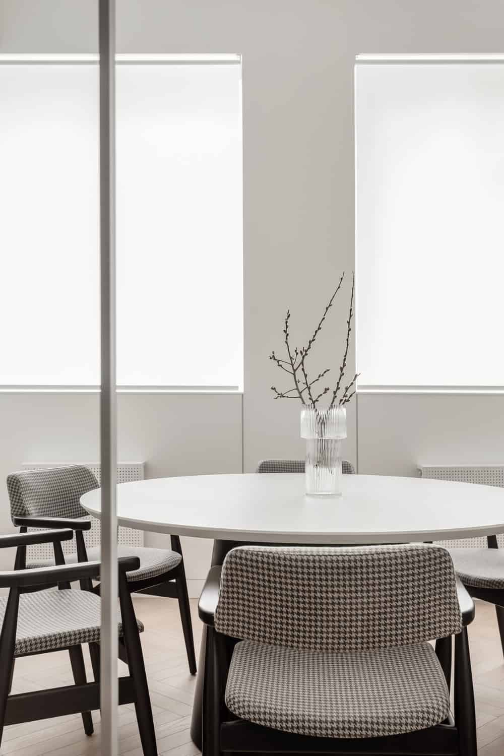 The bright tone of the round table is complemented by the two large windows on the far side of the room.