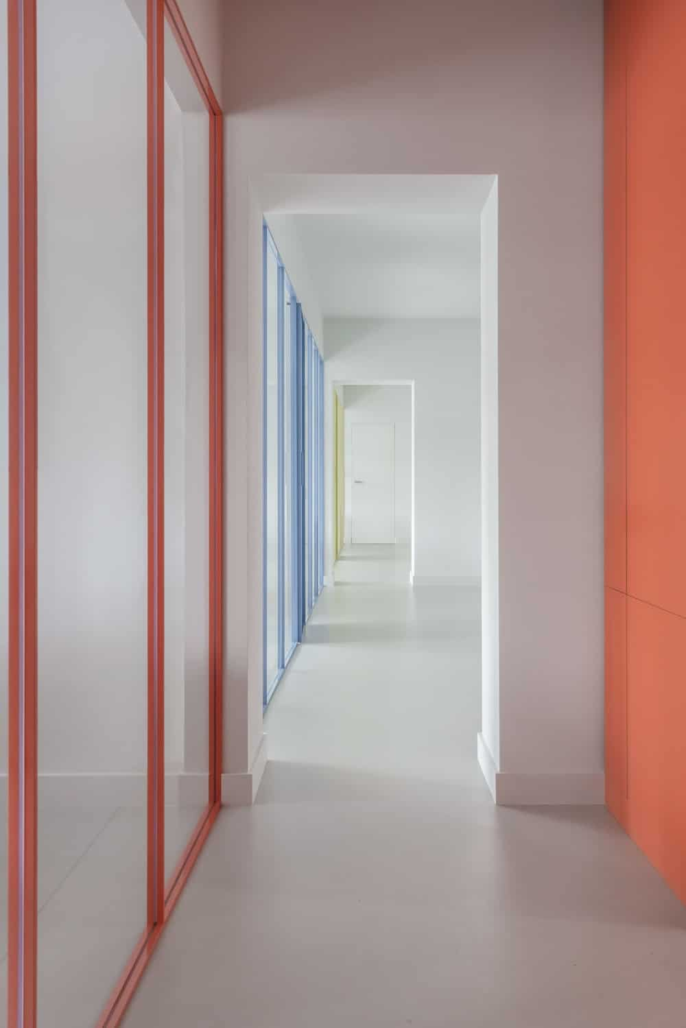 This is a hallway with glass walls on one side that has colorful frames that stand out against the bright tones.