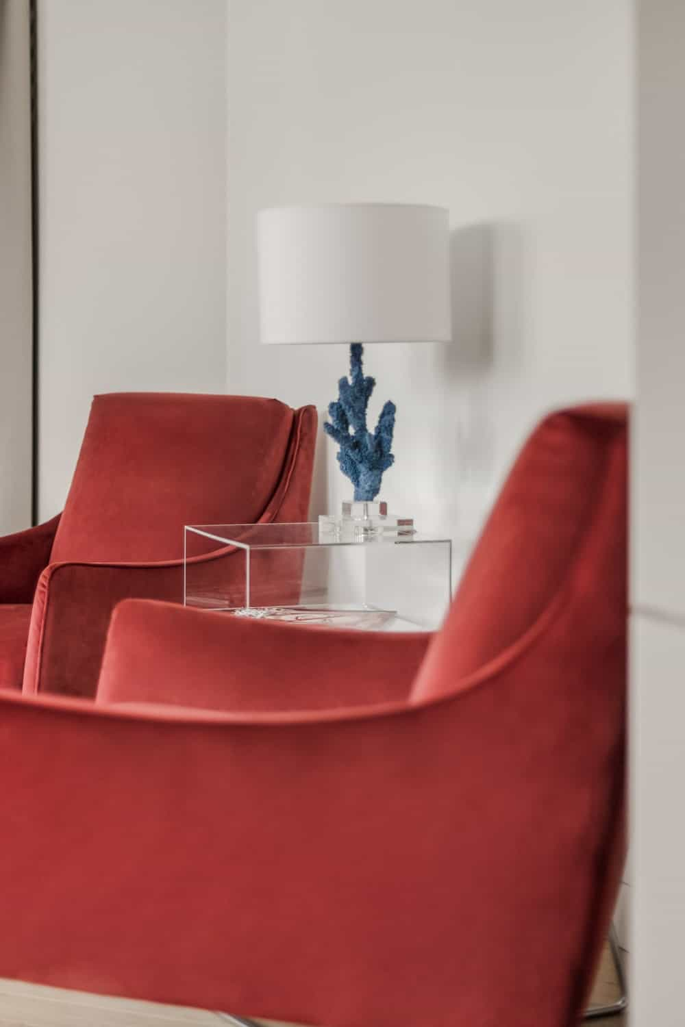 In between these two red velvet arm chairs is a glass modern side table with a table lamp on top.