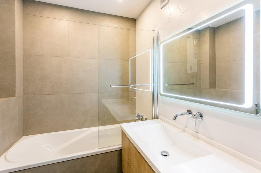 The bathroom has a beige countertop to match the walls. There is also a shower area and bathtub at the far end bordered with a half glass wall.