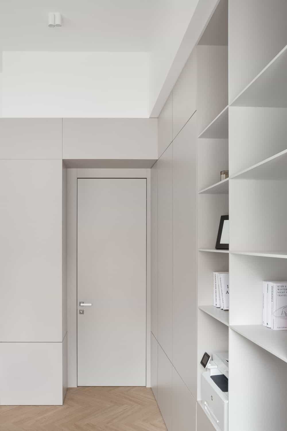 This is a look at the large office with built-in light beige shelves and a door on the far side with the same tone as the walls.