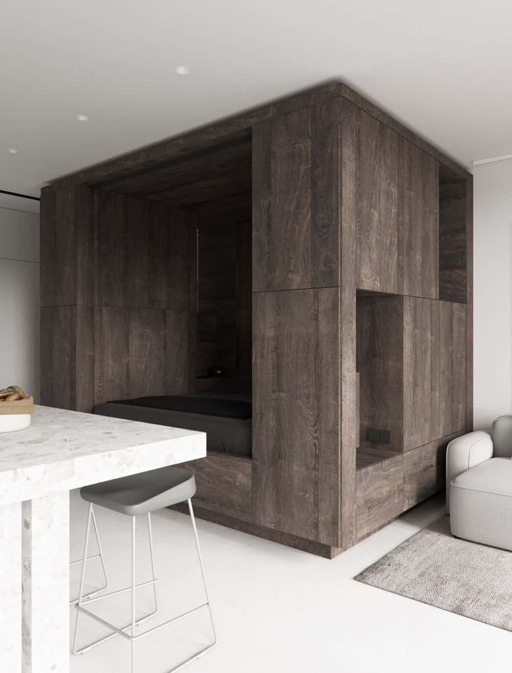This view shows that the kitchen island is paired with stools and on the other side is a large wooden structure that houses the bed and also serves as a shelving for the living room.
