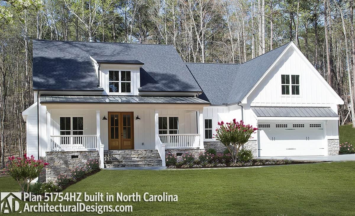 Modern exterior showcasing vertical siding, stone accents, and a porch bordered by white columns and railings.