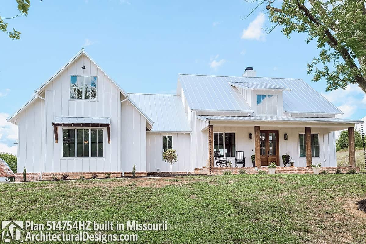 Classic farmhouse exterior with white siding, a dormer window, and a covered porch lined with wooden columns.