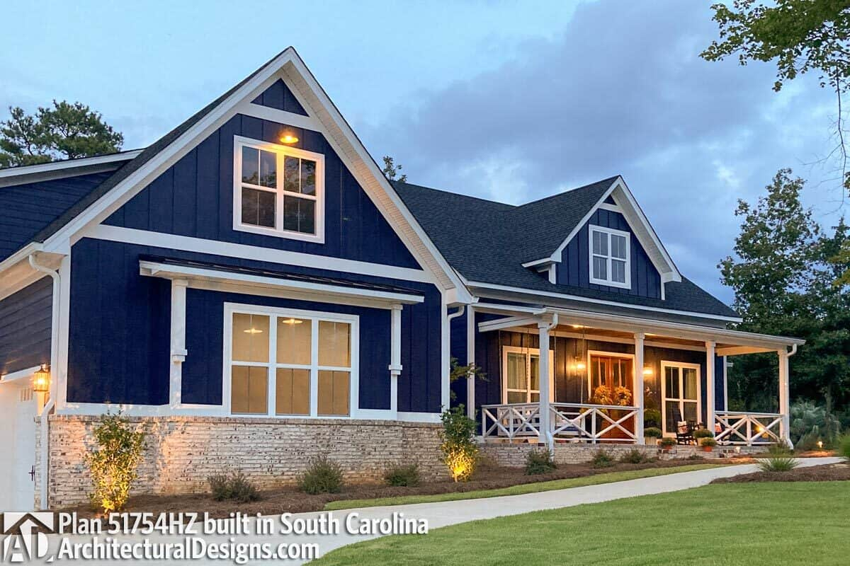 Alternative front exterior with dark blue vertical siding, white-framed windows, stone bases, and a covered porch enclosed in white railings that are arranged in a crisscross pattern.