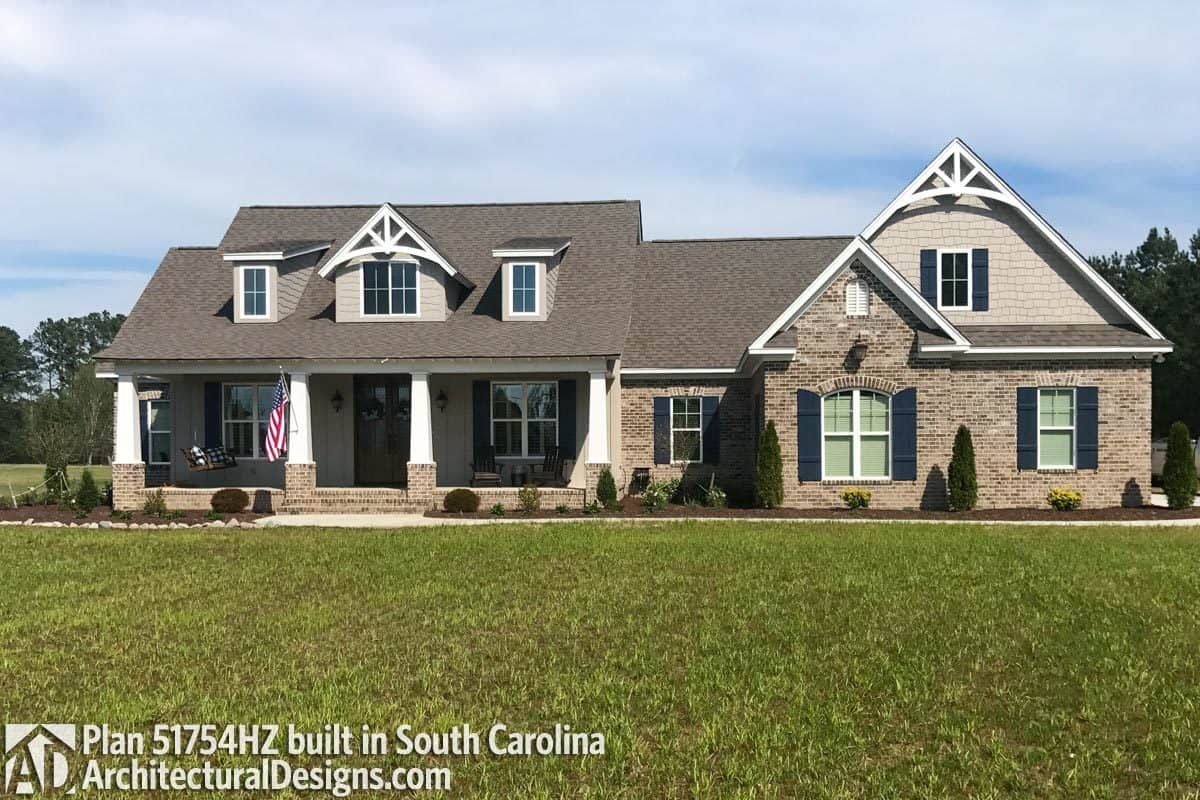 This home facade showcases a stone brick exterior, tapered columns, barn shutters, and gable rooflines graced with decorative white trims.